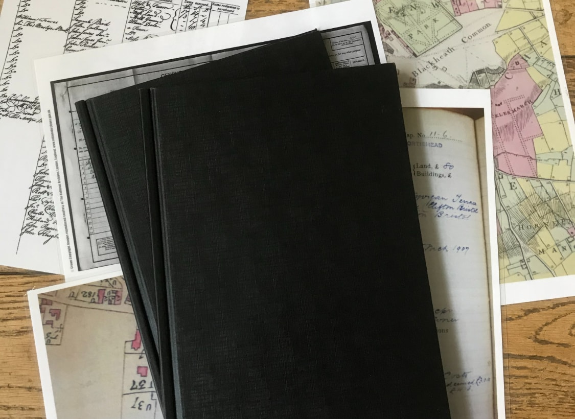 black front cover book with maps around the book on wooden table